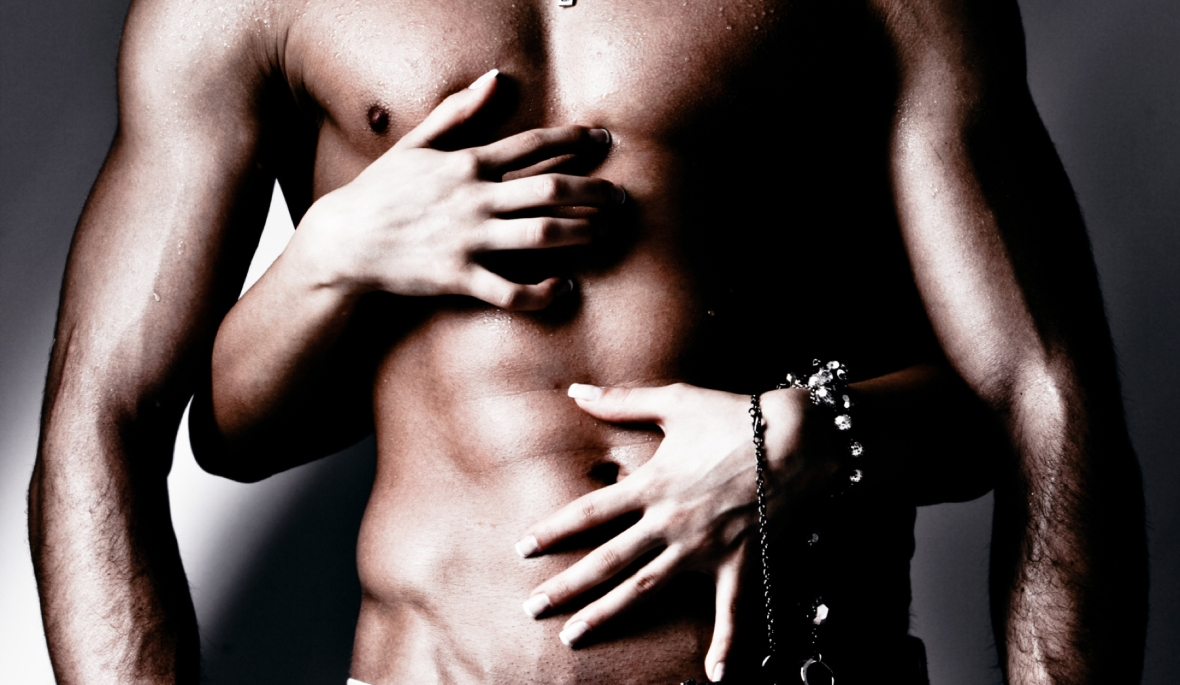 shirtless wet muscular man in jeans and woman hands, studio shot